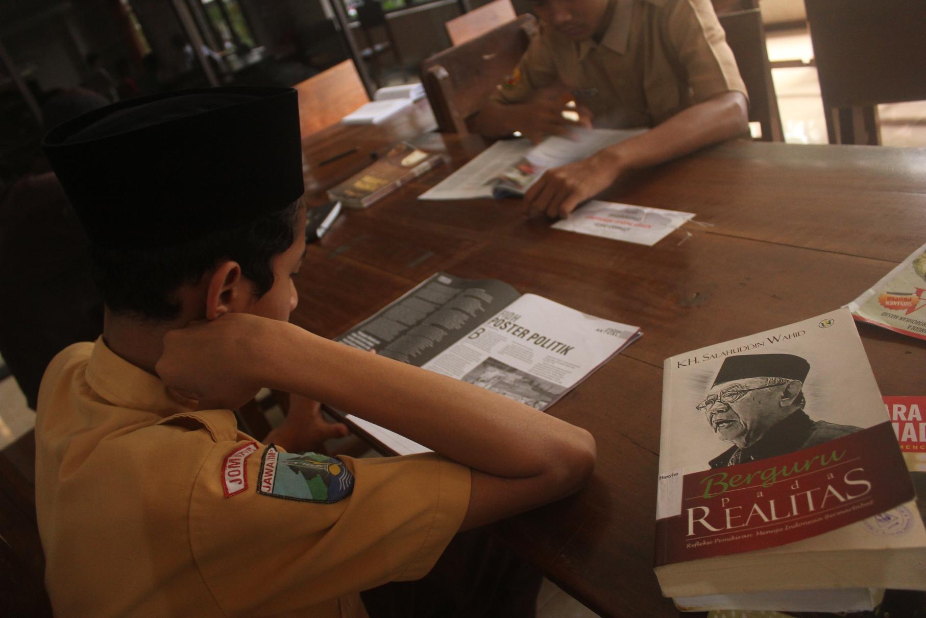 Seorang santri Pesantren Tebuireng membaca Majalah Tebuireng di Perpus Pesantren dan disampaingnya ada buku Belajar dari Realitas karya KH. Salahuddin Wahid pengasuh pesantren antrian buku untuk dibaca selanjutnya.