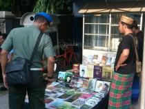Cak Jambeng sedang melayani seorang perwira TNI saat memilih-milih buku yang akan dibeli